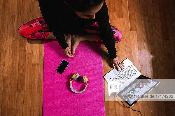 Young woman sitting on yoga mat  having video call on laptop
