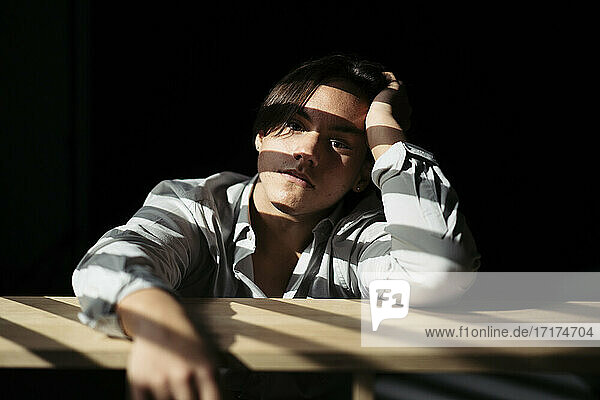Teenage boy sitting at table in dark interior with sunlight