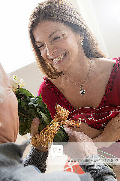 Senior man giving woman bunch of flowers and chocolates