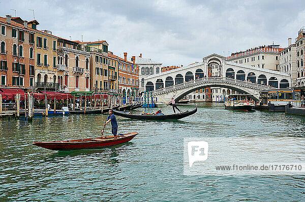 Gondeln vor typischer venezianische Haeuserfassaden am Canale Grande und Rialtobruecke im Hintergrund  Venedig  Venetien  Italien |gondolas in front of typical Venetian house facades on the Grand Canal and Rialto bridge in the back  Venice  Veneto  Italy|
