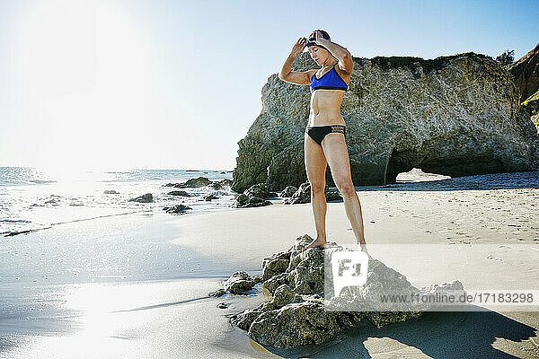 Young woman  triathlete in training in swimwear  swimhats and goggles on a beach.