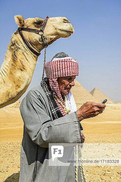 Ein Führer in traditioneller arabischer Kleidung  Gewand und Turban  der ein Mobiltelefon benutzt  und sein Kamel.