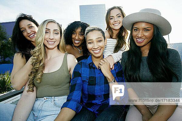 Eine Gruppe junger Frauen  die in der Abenddämmerung auf dem Dach einer Stadt feiern