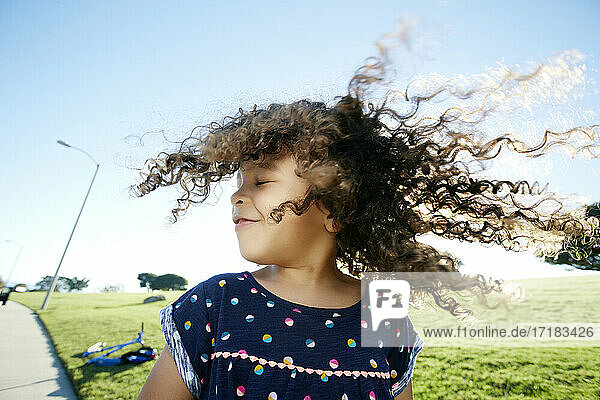Young mixed race girl aged 4 outdoors  curly hair fanning out