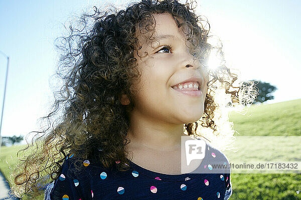 Young mixed race girl aged 4 outdoors