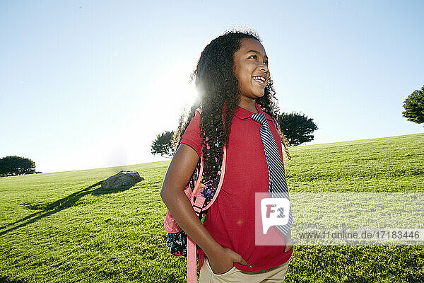 Young mixed race girl in pink shirt and formal tie  wearing a backpack