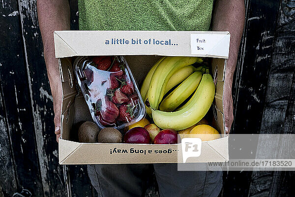 Close up of person holding an organic fruit and vegetable box with a selection of fresh produce.