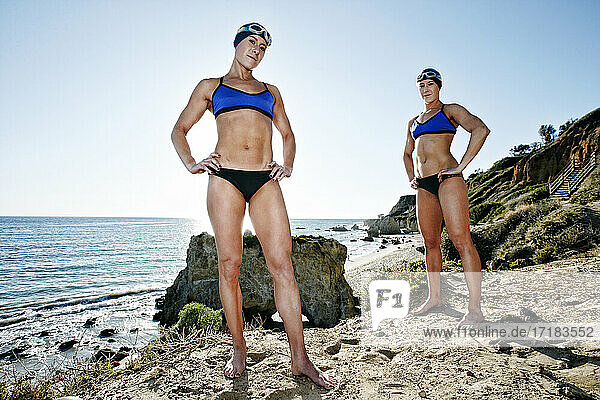 Two sisters  triathletes in training in swimwear  swimhats and goggles.