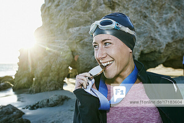 Young woman,  triathlete in jacket biting a large medal with her teeth,  a winner
