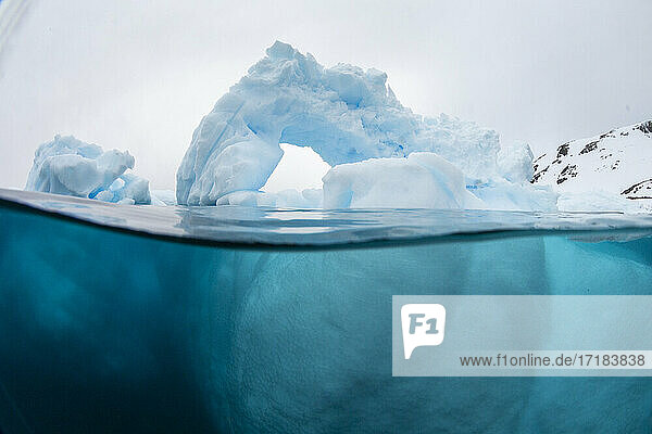 Above and below view of an arch formed in an iceberg at Cuverville Island  Ererra Channel  Antarctica  Polar Regions