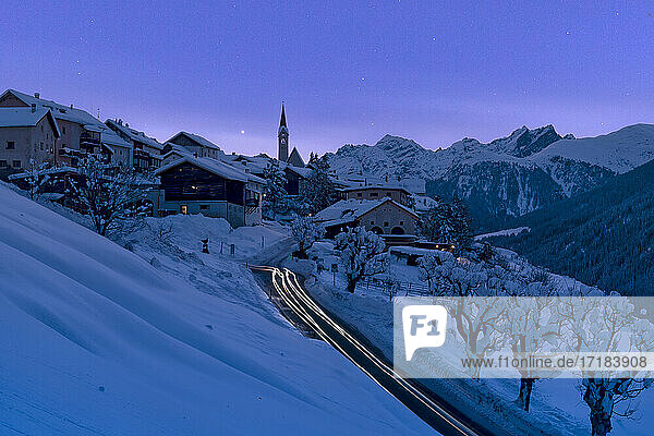 Snow covered village of Guarda lit by car trail lights during a blue winter dusk  Lower Engadine  Graubunden Canton  Switzerland  Europe
