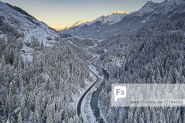 Sunrise over winding mountain road and frozen river in the forest covered with snow  Zernez  Graubunden Canton  Switzerland  Europe