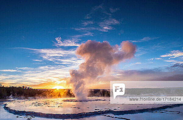 Great Fountain Geyser at sunset with reflection and sunburst  Yellowstone National Park  UNESCO World Heritage Site  Wyoming  United States of America  North America