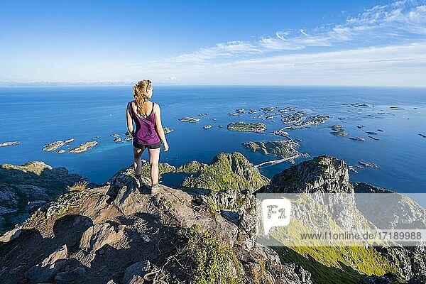 Kleine Felsinseln im Meer  Wanderin blickt vom Gipfel des Berges Festvågtind auf Ort Henningsvær  Vågan  Lofoten  Nordland  Norwegen  Europa