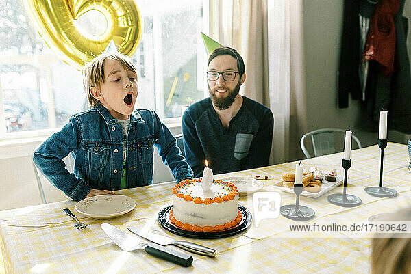 Little boy blowing out candle on his birthday cake at table with dad
