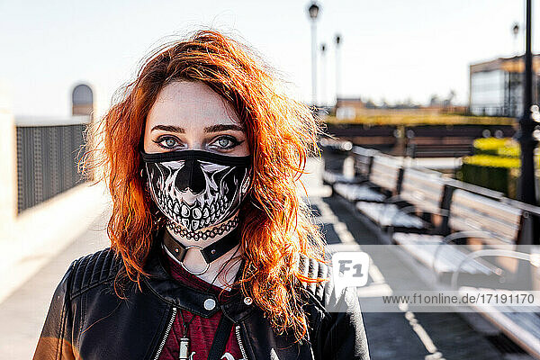 Portrait of gothic girl with orange hair and skull face mask