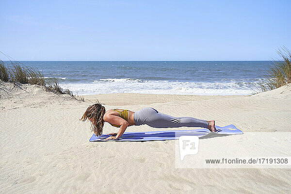 young girl performs planks on the beach in the morning.