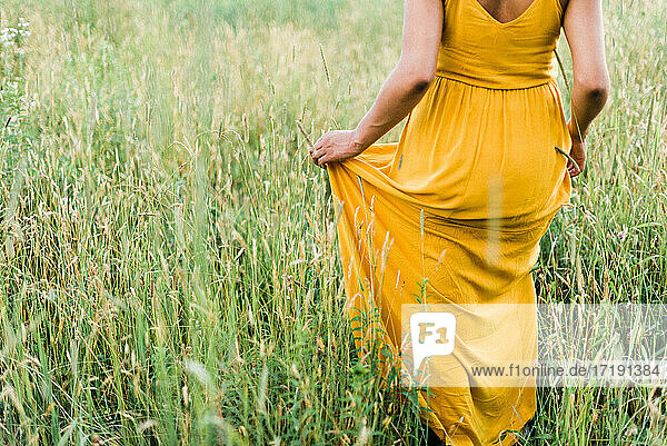 Portrait of a black woman in a field during summer sunset