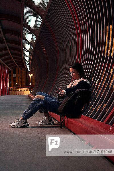 Young woman is looking at her telephone on a red bridge at night