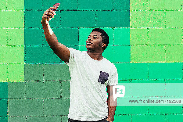 Black afro american boy on green background taking a selfie with his mobile phone.
