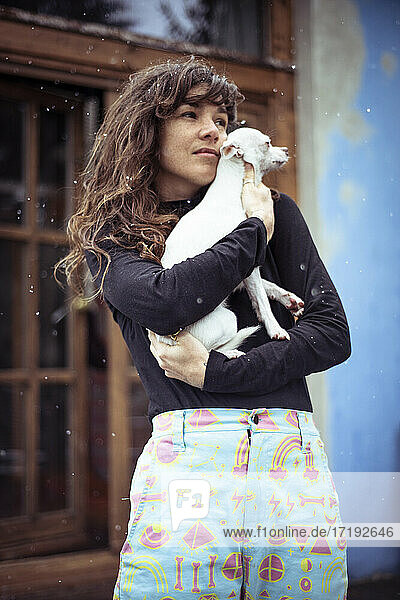 Woman with snow in hair holds small white dog to stay warm outside