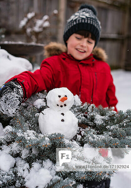 Boy looking at a small snowman on a shrub outdoors on a snowy day.