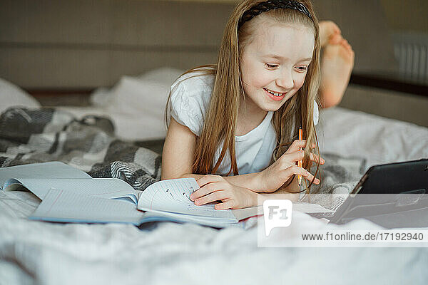 girl lying on the bed surrounded by notebooks