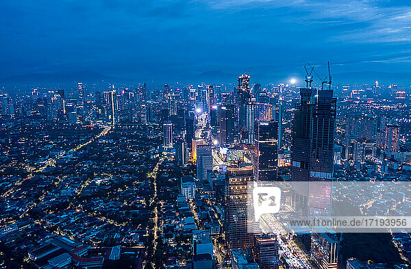 Aerial wide panoramic view of modern cityscape with high rises in the night Skyscrapers and residential neighborhoods in blue night light in Jakarta  Indonesia