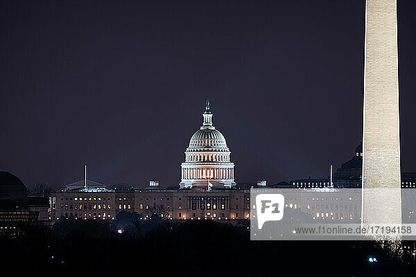 The US Capitol building and the Washington Monument at night.