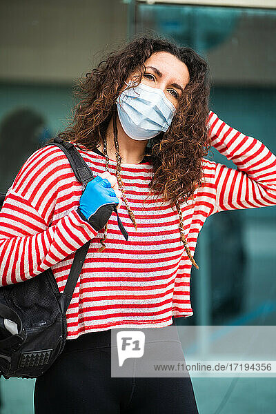 Content woman with bag and mask standing in city