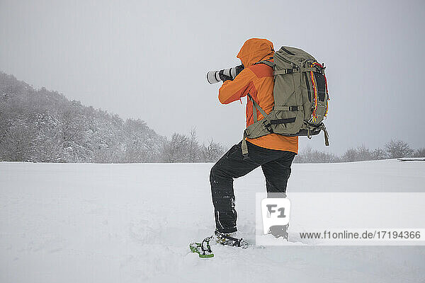 photographer working with snowshoes in covered field