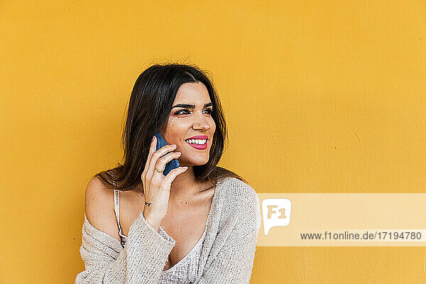 Portrait of Spanish brunette girl talking on mobile phone on yellow background wall.