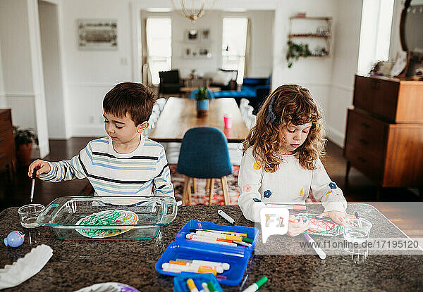 Young brother and sister coloring with markers at kitchen counter