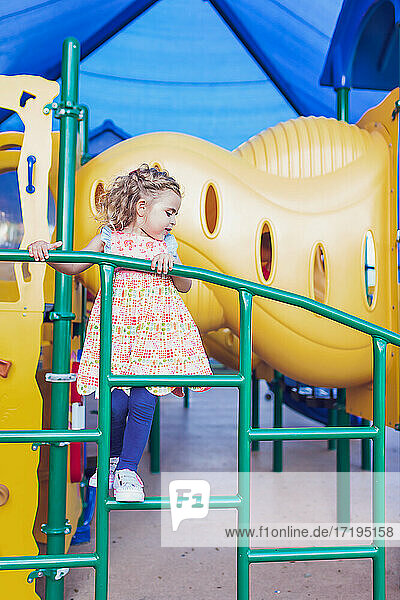 Preschooler girl climbing on a structure at a public playground.