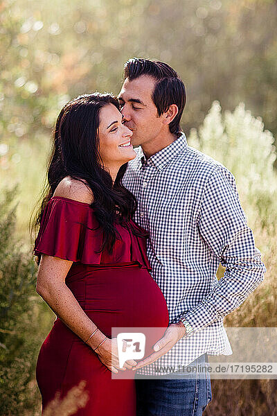 Husband Kissing Expectant Wife in Field in San Diego