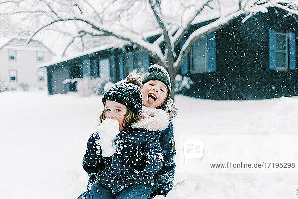 Two children eating snow and playing together in nor'easter storm