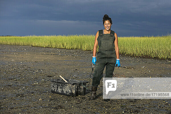 Portrait of asian female oyster picker in waders smiling at camera