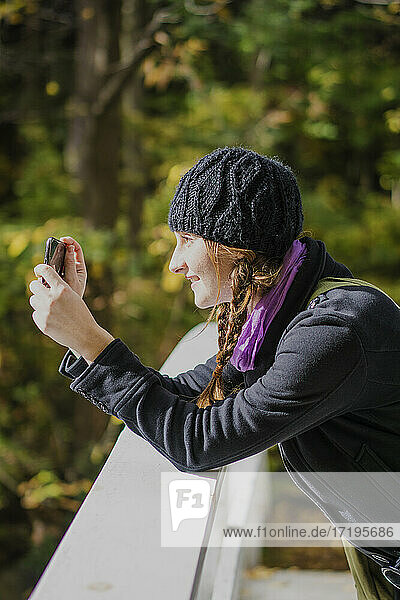 Solo woman traveller using smartphone to take pictures