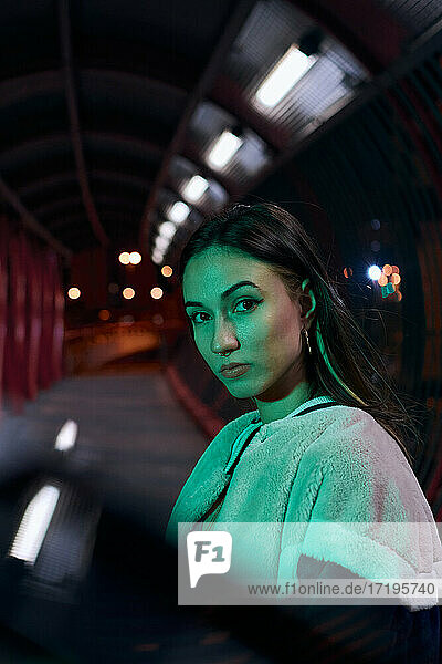 A young woman looks at camera illuminated by a green light at night