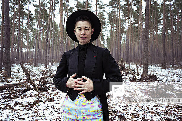 Queer trendy woman stands in white european forrest during winter