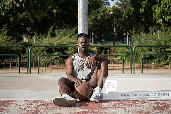 Black man resting on basketball court