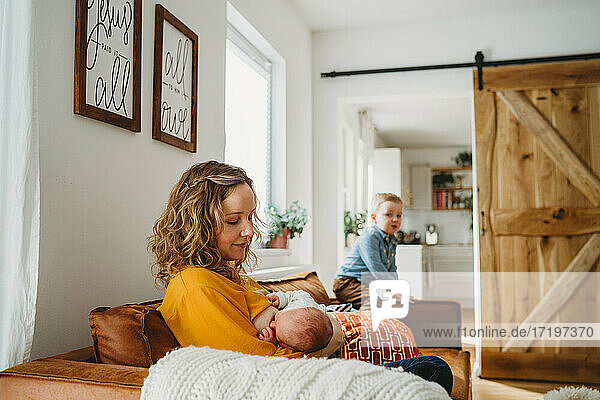 Mother breastfeeding newborn baby at home in family room with son Mother breastfeeding newborn baby at home in family room with son