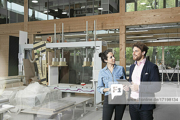 Geschäftsfrau  die einen männlichen Kollegen mit einem digitalen Tablet betrachtet  während sie in einer Fabrik steht