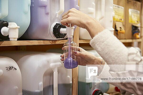 Frau füllt lilafarbene Flüssigkeit aus dem Zuckerrohr in eine Flasche im Geschäft Frau füllt lilafarbene Flüssigkeit aus dem Zuckerrohr in eine Flasche im Geschäft