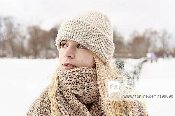 Beautiful girl wearing knit hat looking away during winter