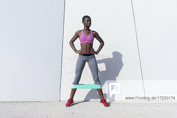 Fit young woman with rubber band doing leg exercise while standing against white wall