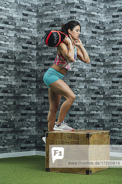 Female athlete practicing with punching bag in gym
