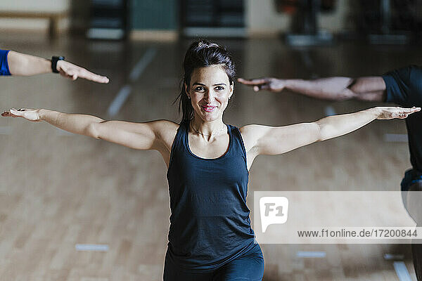 Smiling sportswoman in warrior position exercising with male friends in gym