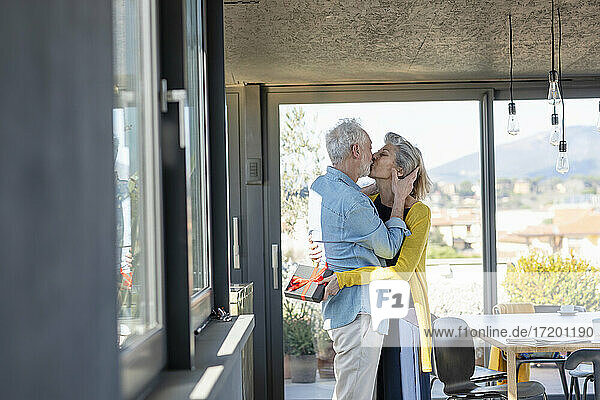 Ältere Frau mit Geschenkbox  die einen Mann küsst  während sie zu Hause steht