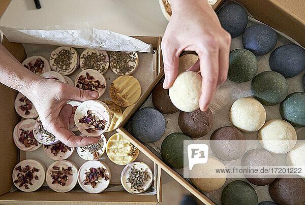 Die Hände einer Unternehmerin halten handgemachte Seifen über dem Tisch Die Hände einer Unternehmerin halten handgemachte Seifen über dem Tisch